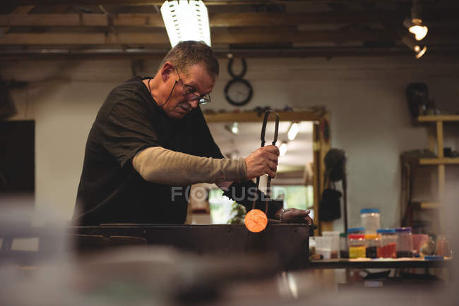 Glassblower shaping molten glass at glassblowing factory — Stock Photo