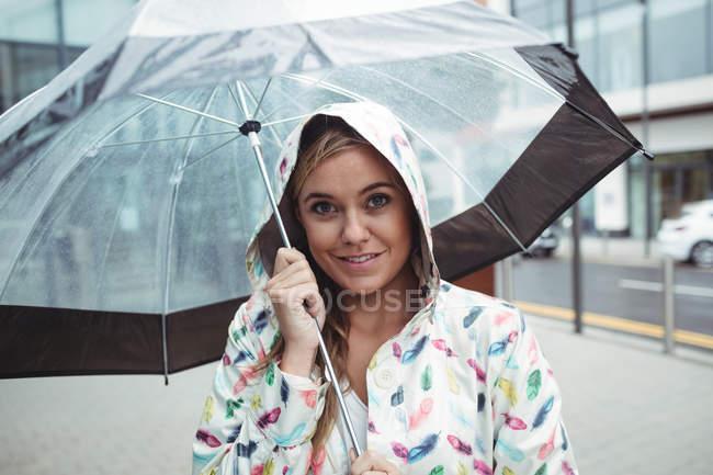 Portrait de belle femme tenant parapluie pendant la saison des pluies et regardant la caméra — Photo de stock