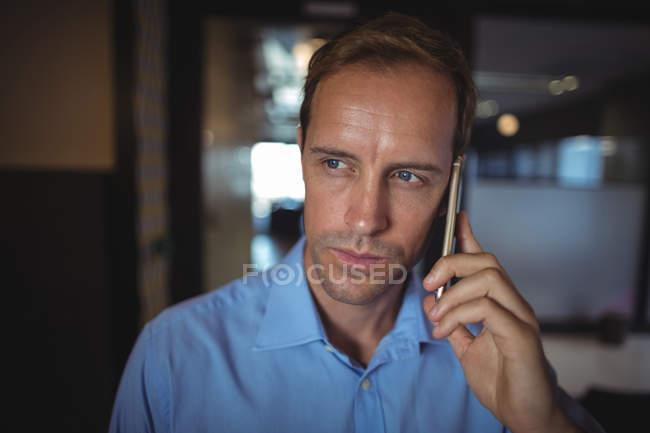 Empresário falando no celular no escritório — Fotografia de Stock
