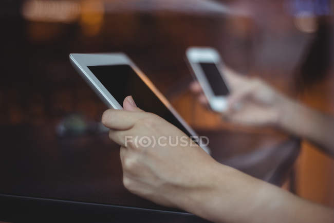 Close-up of woman using mobile phone and digital tablet in cafe — Stock Photo