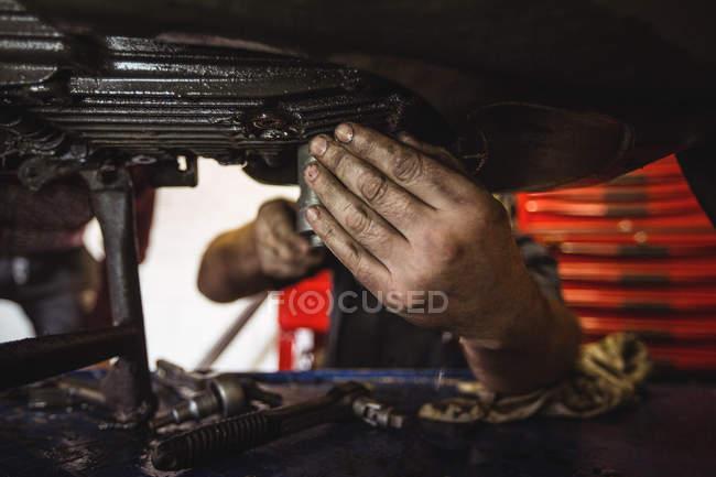 Close-up of mechanic examining motorbike at workshop — Stock Photo