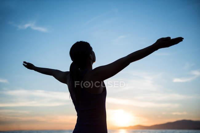 Femme effectuant du yoga sur la plage pendant le coucher du soleil — Photo de stock