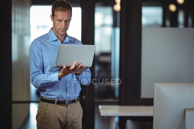 Homme d'affaires réfléchie à l'aide d'ordinateur portable au bureau — Photo de stock