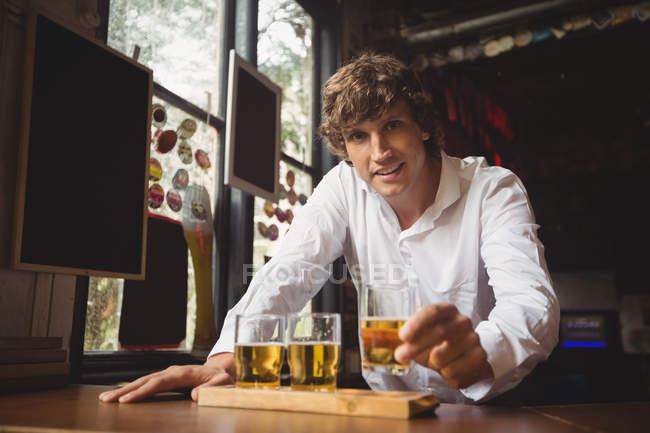 Portrait of bartender holding whisky shot glass at bar counter in bar — Stock Photo