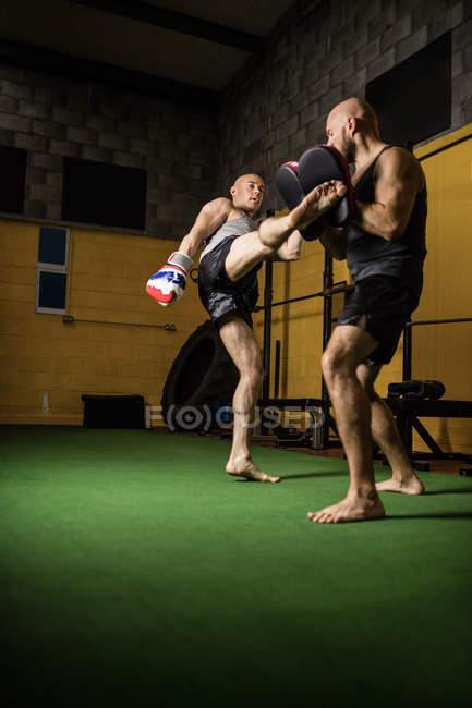 Vue à faible angle de deux boxeurs thaïlandais pratiquant la boxe dans la salle de gym — Photo de stock