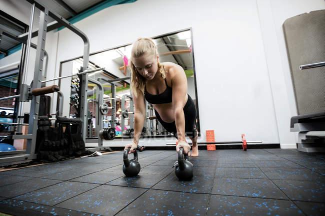 Mujer embarazada haciendo flexiones con campanas de caldera en el gimnasio - foto de stock