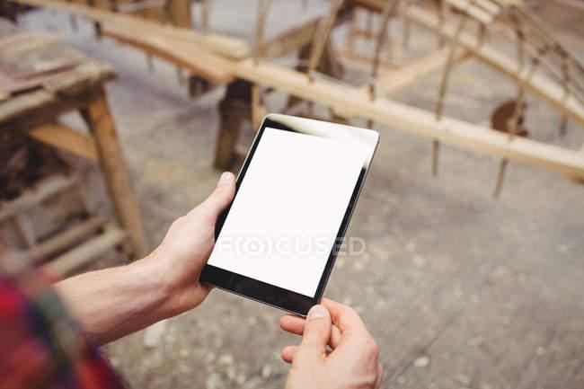 Hands of man using digital tablet in boatyard — Stock Photo
