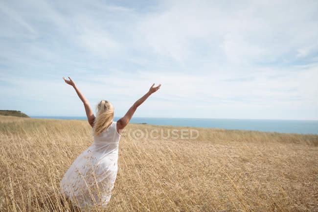 Задній вид блондинка жінку, що стояли в полі з розкритими обіймами — стокове фото