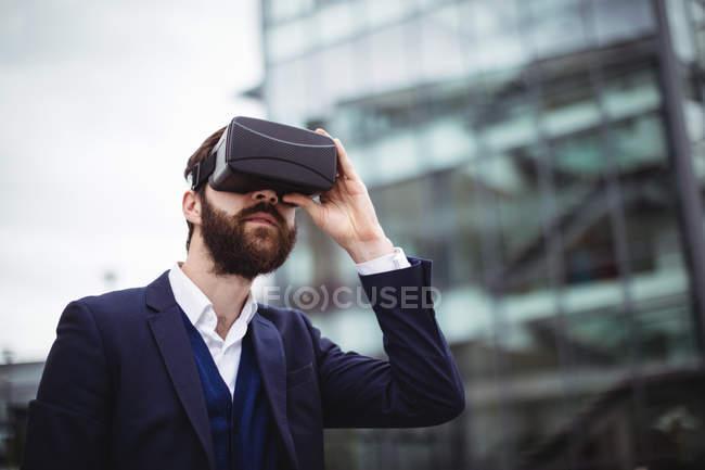 Businessman using virtual reality headset outside office — Stock Photo