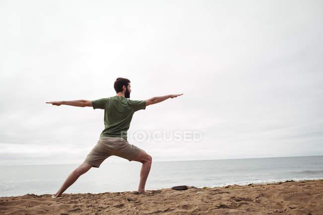 Задний вид человека, выполняющего упражнения на растяжку на пляже — стоковое фото