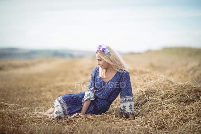 Bela mulher loira em vestido azul sentado em campo — Fotografia de Stock