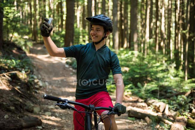 Чоловічий велосипедист бере selfie на мобільний телефон у лісі — стокове фото