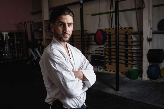 Portrait of man in karategi standing with arms crossed in fitness studio — Stock Photo