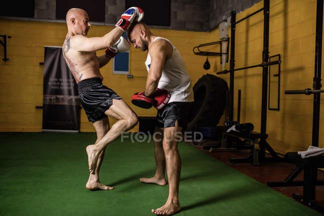 Vue latérale de deux boxeurs thaïlandais pratiquant dans la salle de gym — Photo de stock
