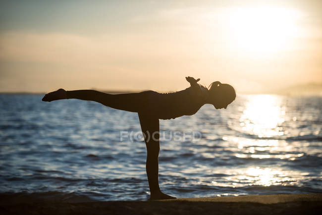 Side view of Woman performing yoga on beach during sunset — Stock Photo