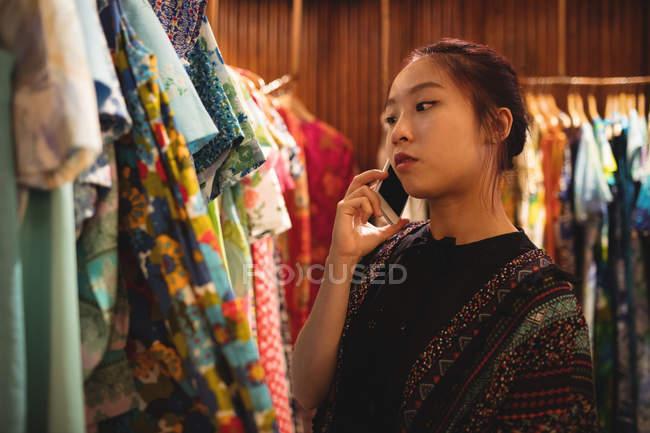Donna parla al cellulare mentre si selezionano i vestiti sui ganci presso negozio di abbigliamento — Foto stock