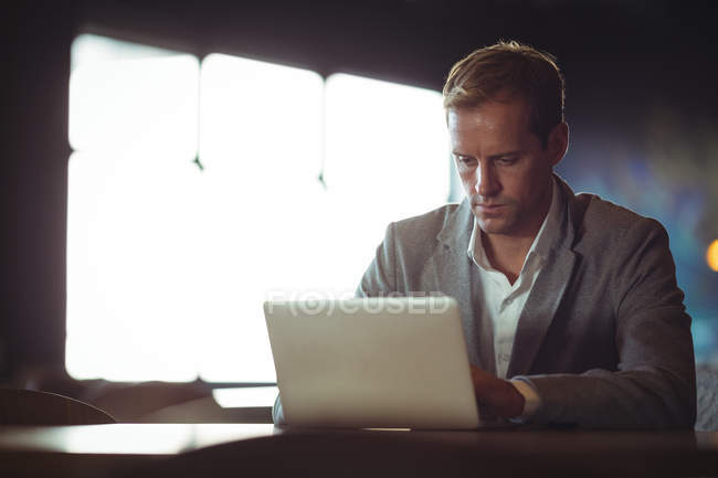 Business man using laptop at desk in office — Stock Photo