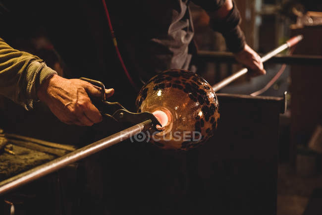 Glassblower holding blowpipe with diamond shears at glassblowing factory — Stock Photo