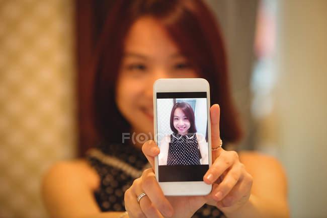 Femme tenant une photo de téléphone portable à la boutique magasin — Photo de stock