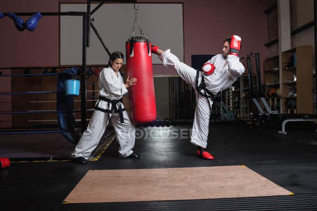 Seitenansicht von Mann und Frau beim Karate mit Boxsack im Studio — Stockfoto