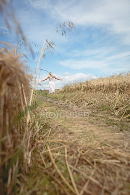Selective focus of blonde woman standing in field with open arms — Stock Photo