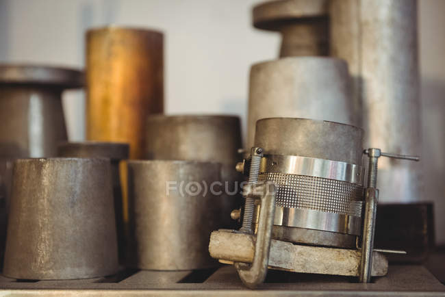 Metal molds for glassblowing arranged on shelf at glassblowing factory — Stock Photo