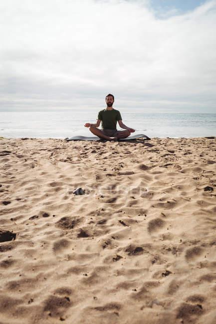 Homme effectuant du yoga sur la plage — Photo de stock