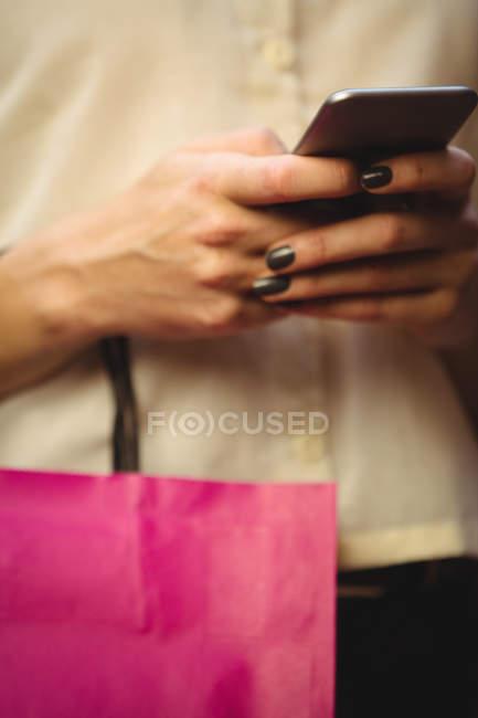 Milieu de la section de la femme en utilisant le téléphone mobile tout en faisant des achats en boutique — Photo de stock