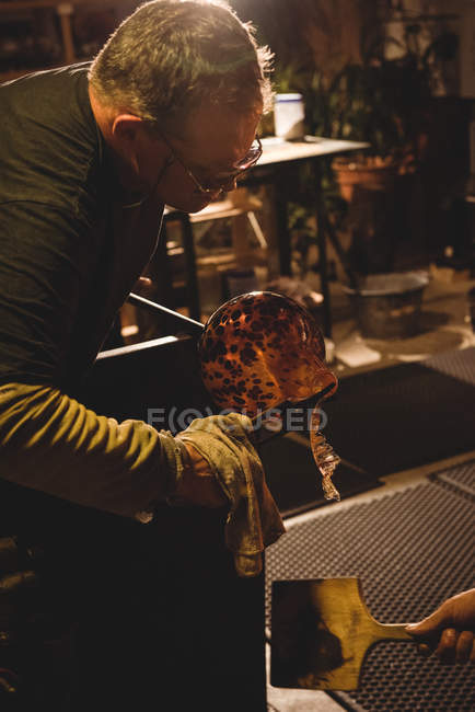 Team of glassblowers shaping a molten glass at glassblowing factory — Stock Photo