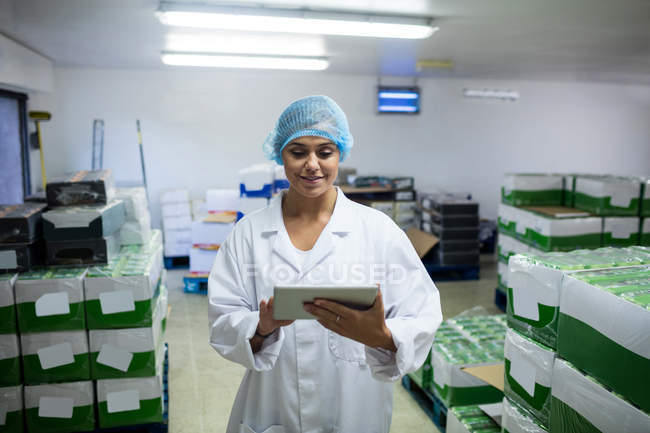Female staff using digital tablet in egg factory — Stock Photo