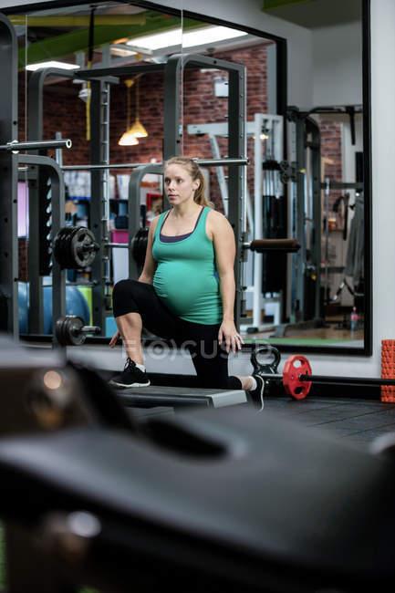 Mujer embarazada realizando ejercicio en el gimnasio - foto de stock