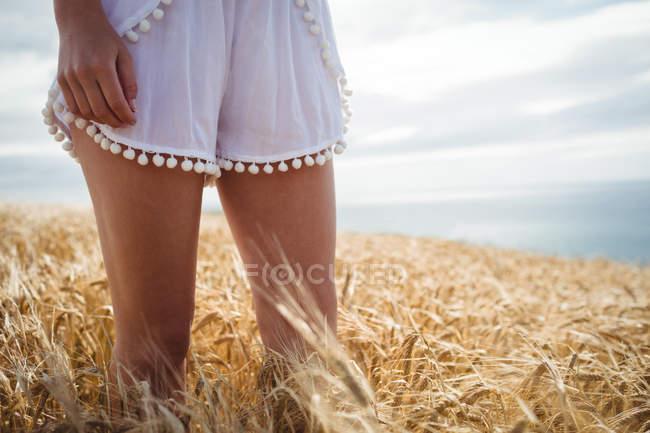Міделю жінка, стоячи в пшеничному полі на сонячний день — стокове фото