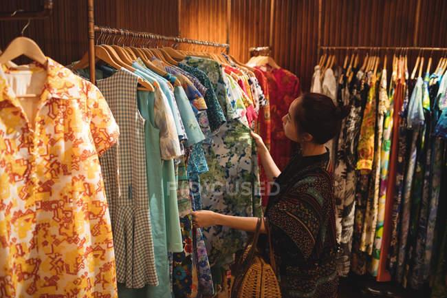 Mujer seleccionando ropa en perchas en la tienda de ropa - foto de stock
