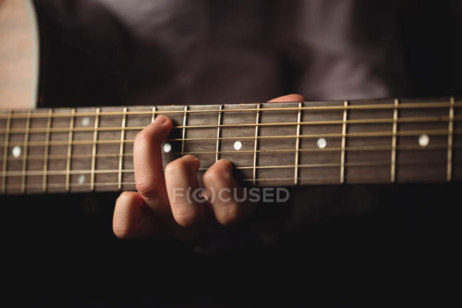 Close-up of woman playing a guitar in music school — Stock Photo
