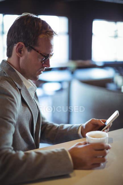 Бізнесмен, за допомогою мобільного телефону під час за кавою в кафе — стокове фото