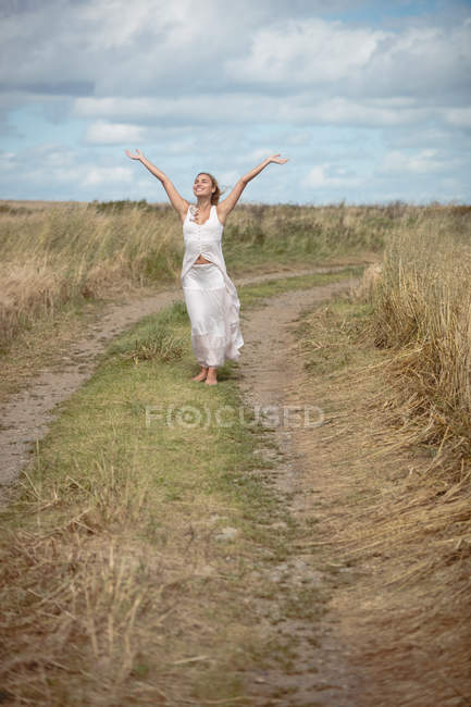 Mulher loira despreocupada em pé no caminho de campo com braços levantados — Fotografia de Stock