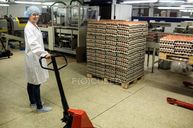 Personnel féminin tenant un cric à palette dans une usine d'œufs — Photo de stock