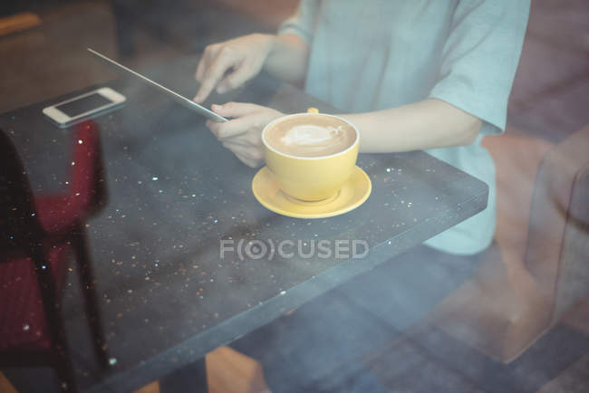 Woman using digital tablet while having coffee in cafe — Stock Photo