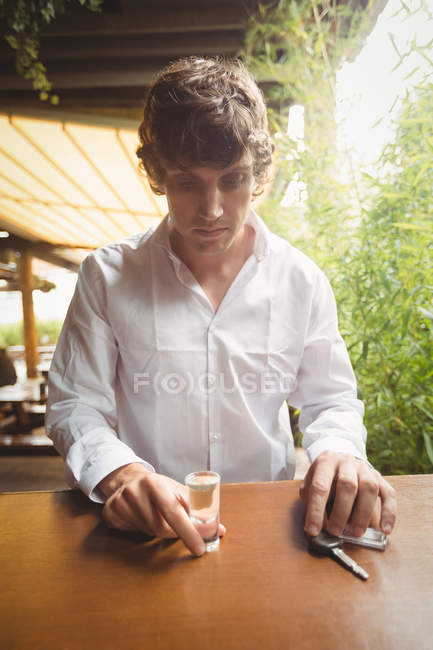 Thoughtful man holding glass of tequila shot in bar counter at bar — Stock Photo