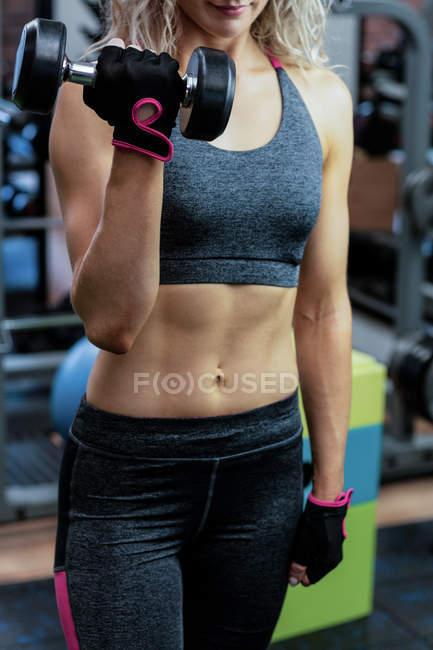 Женщина поднимает гантели в спортзале — стоковое фото