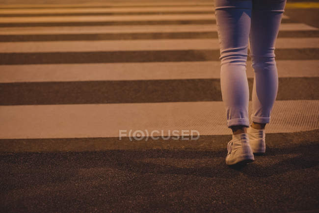 Low section of woman walking on zebra crossing at night — Stock Photo