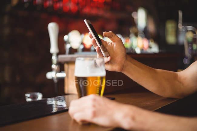 Людина з келих пива, що використання мобільного телефону у лічильник в барі — стокове фото