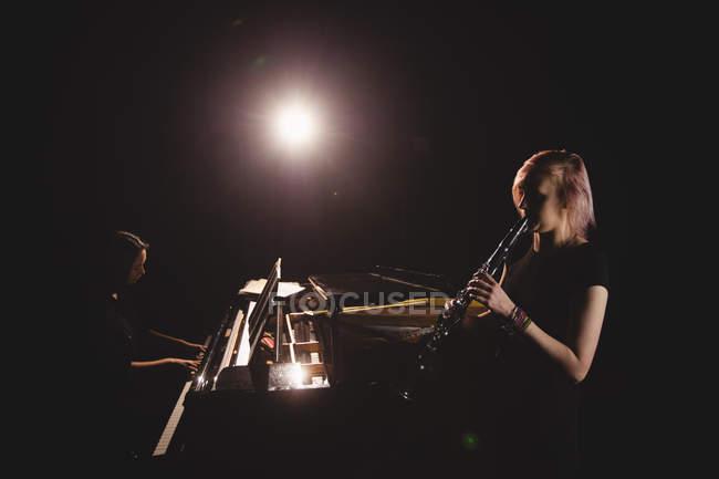 Студенты, играющие на кларнете и пианино в музыкальной школе — стоковое фото