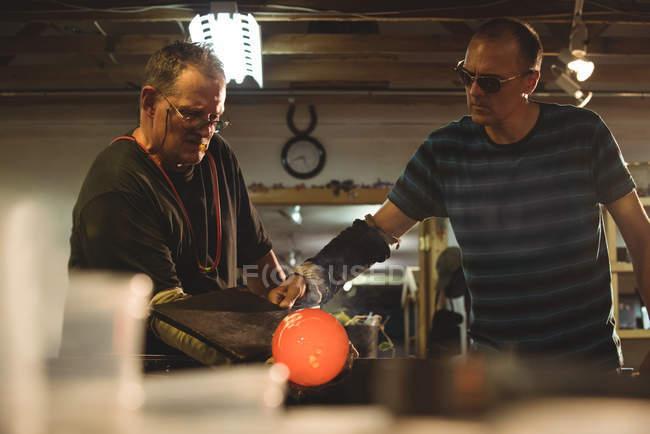 Команда стеклодувов, формирующих расплавленное стекло на стекольном заводе — стоковое фото