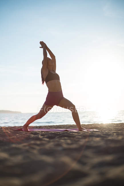 Surface level of Woman performing yoga on beach on sunny day — Stock Photo