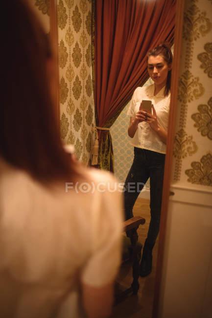 Femme utilisant un téléphone portable au magasin boutique — Photo de stock