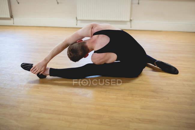 Вид на балерино, растянувшийся на деревянном полу в балетной студии — стоковое фото