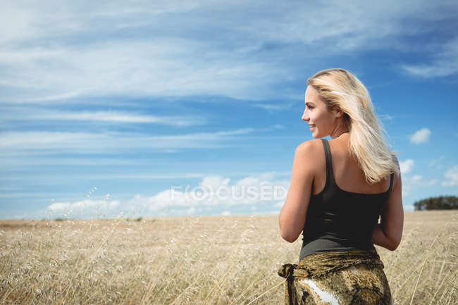 Rear view of smiling blonde woman standing in field — Stock Photo