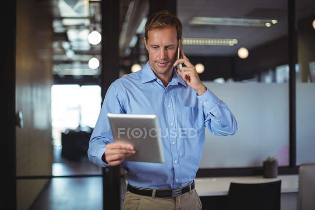Empresário olhando para tablet digital enquanto fala no celular no escritório — Fotografia de Stock