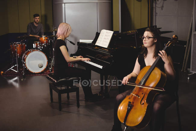 Group of students playing double bass, drum set and piano in a studio — Stock Photo